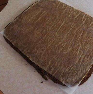 Вытащить корж и накрыть его вторым листом бумаги.