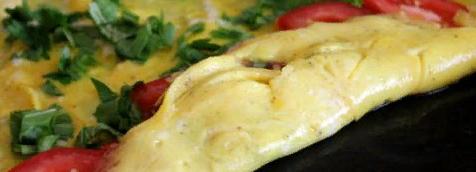 Аккуратно лопаточкой свернуть омлет в рулет со стороны томатов, сразу снять с огня.